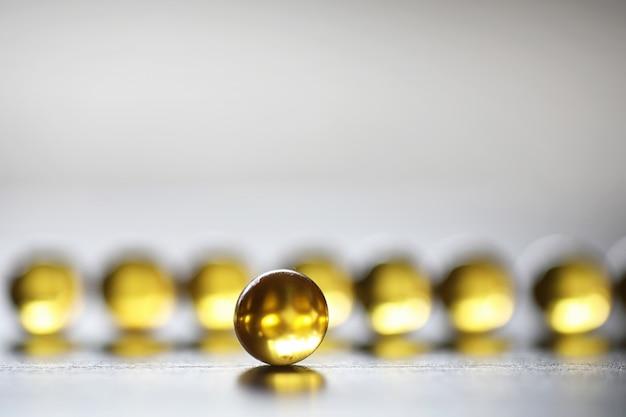 Tłuszcz rybny. produkty medyczne do leczenia chorób. pojęcie uzależnienia zdrowotnego od tabletów. kapsułki oleju rybnego na podłoże drewniane.