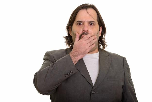 Tłuszczu biznesmen kaukaski patrząc w szoku, obejmując usta na białym tle