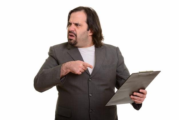 Tłuszczu biznesmen kaukaski patrząc zły, wskazując i trzymając schowek