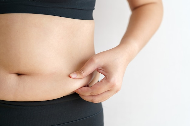 Tłuszczu brzucha kobiet. otyła kobieta ręka trzyma nadmierny tłuszcz z brzucha. koncepcja stylu życia diety
