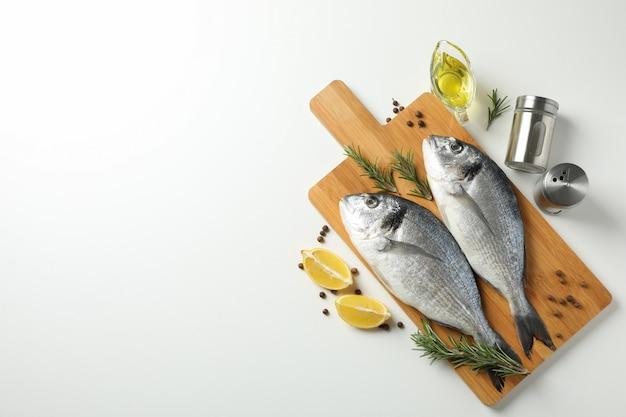 Tnąca deska z dorado ryba i kulinarnymi składnikami na białym tle, odgórny widok