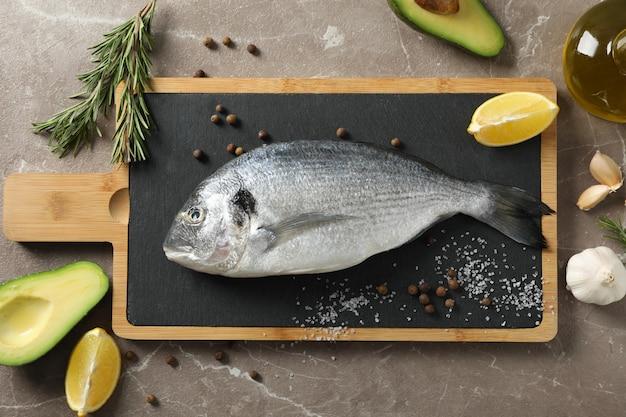 Tnąca deska z dorado ryba i kulinarnymi składnikami na szarym tle, odgórny widok