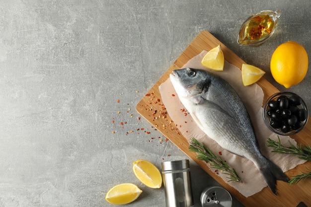 Tnąca deska z dorado ryba i pikantność na szarym tle, odgórny widok