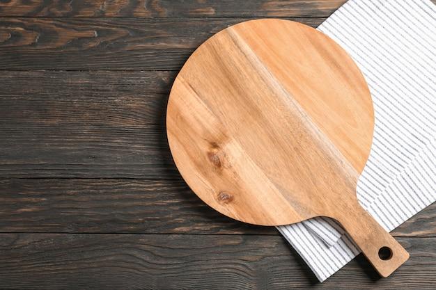 Tnąca deska z kuchennym ręcznikiem na drewnianym tle, przestrzeń dla teksta