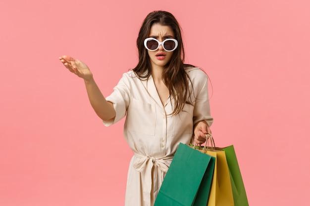 To całkowita śmieci, wtf. rozczarowana i zaniepokojona sassy glamour młoda zakupoholiczka, kobieta w sukni trzyma torby na zakupy, wskazując na coś obrzydliwego, pokaż potępienie lub pogardę