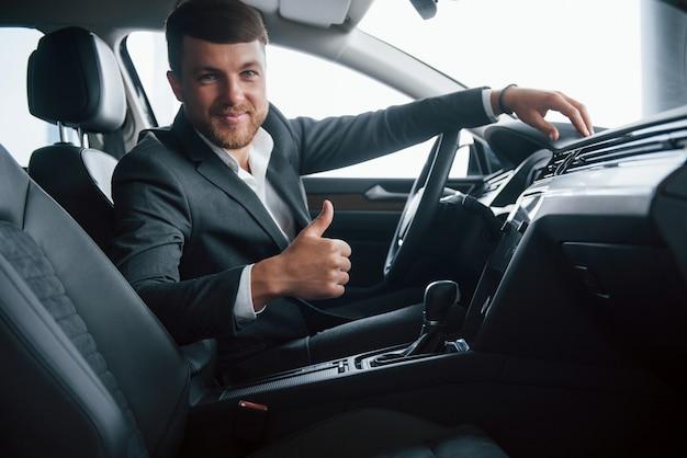 To cudownie. nowoczesny biznesmen próbuje swojego nowego samochodu w salonie samochodowym