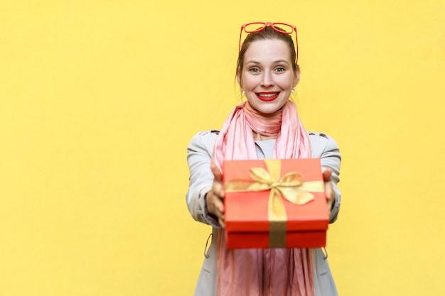 To dla ciebie. kobieta dostawy trzyma pudełko. studio strzał na żółtym tle