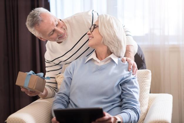 To dla ciebie. zadowolony szczęśliwy starszy mężczyzna trzymający prezent stojąc obok sofy i przytulając żonę