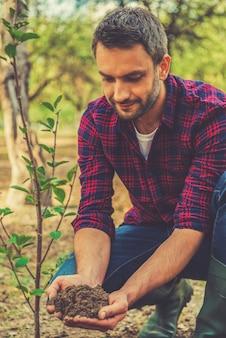 To dobra gleba. pewny siebie młody mężczyzna trzyma ziemię i patrzy na nią podczas pracy w ogrodzie