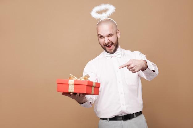 To jest dla ciebie. szczęśliwy zabawny brodaty anioł w średnim wieku w koszuli i białej aureoli na głowie, wskazując na czerwony prezent i mrugając z uśmiechem. kryty strzał studio, na białym tle na jasnobrązowym tle.