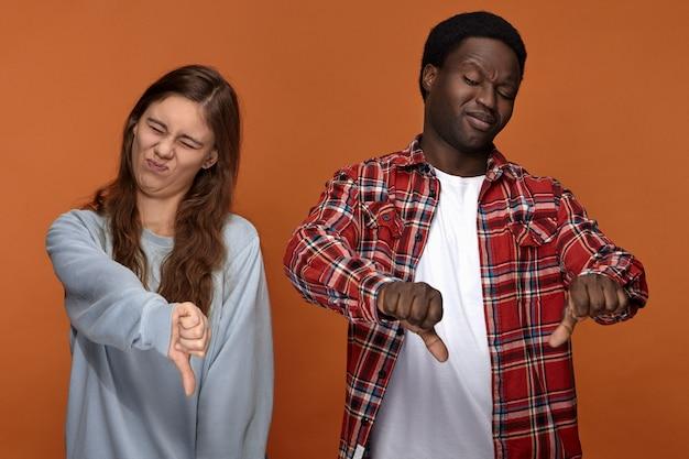 To jest do bani. portret emocjonalnej młodej pary międzyrasowej afrykańska kobieta i mężczyzna rasy kaukaskiej pokazując kciuk w dół gest, zniesmaczony złym jedzeniem lub smrodem, tłumiąc wymioty. niechęć i wstręt