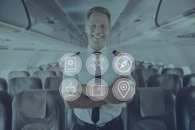 To jest mój samolot. pewny siebie pilot w mundurze trzymający skrzyżowane ręce i uśmiechnięty stojąc wewnątrz samolotu