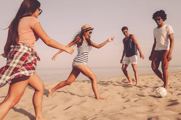 To jest moje! grupa wesołych młodych ludzi bawiących się piłką nożną na plaży z morzem w tle