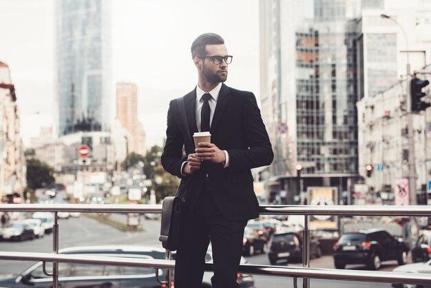 To jest moje miasto. przekonany, młody człowiek w pełnym garniturze, trzymający filiżankę kawy i odwracający wzrok
