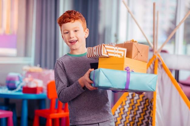 To jest moje. zadowolony rudowłosy chłopiec wyrażający pozytywne nastawienie podczas przyjęcia urodzinowego