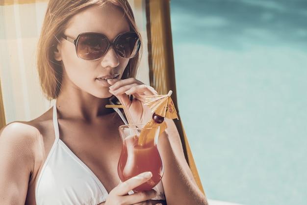 To jest prawdziwe życie! piękna młoda kobieta w białym bikini pije koktajl podczas relaksu na leżaku przy basenie