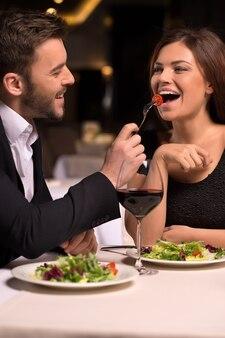 To jest pyszne! piękna młoda para karmiąca się nawzajem i uśmiechnięta podczas spędzania czasu w restauracji