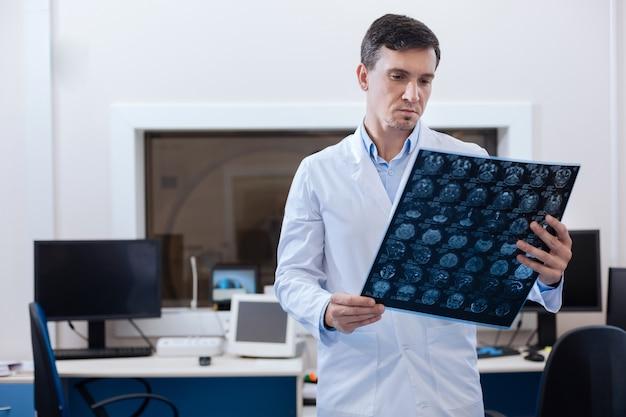To jest rak. profesjonalny, przystojny mężczyzna onkolog patrząc na zdjęcie rentgenowskie i stawiający diagnozę podczas wykonywania swojej pracy
