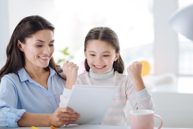 To jest sukces. szczęśliwa radosna pozytywna dziewczyna patrząc na ekran tabletu i mówiąca tak, siedząc razem z matką