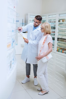 To jest tutaj. skoncentrowany stary gość stojący w pobliżu apteki podczas wybierania niezbędnych tabletek