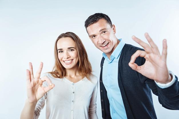 """To jest w porządku. pozytywnie nastawieni biznesmeni, kobiety i mężczyźni, patrząc w kamerę z radosnymi uśmiechami na twarzach i pokazując razem znak """"ok""""."""
