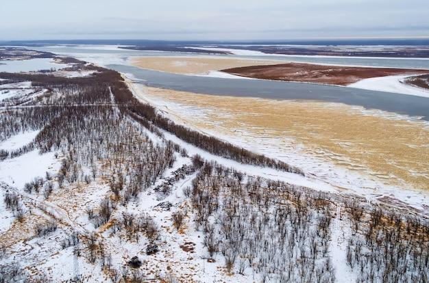 To jest widok z lotu ptaka na las z dużą rzeką w mroźny zimowy dzień.