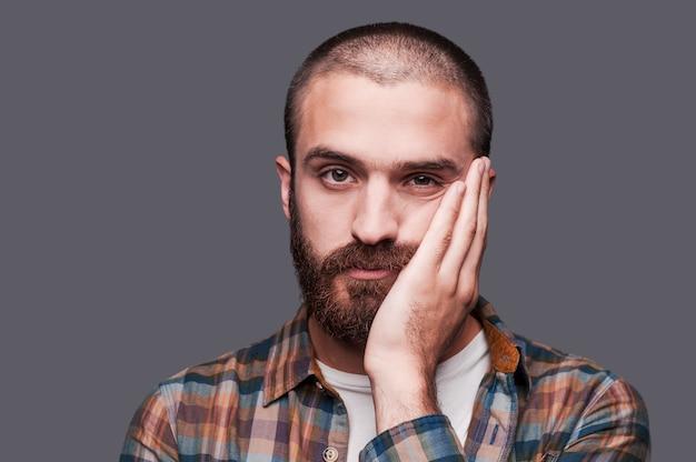 To jest zbyt nudne. znudzony młody brodaty mężczyzna trzymający skrzyżowane ręce i wyrażający ironiczny uśmiech stojąc na szarym tle
