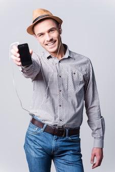 To moja ulubiona piosenka! przystojny młody mężczyzna w fedorze pokazujący odtwarzacz mp3 i uśmiechający się stojąc na szarym tle