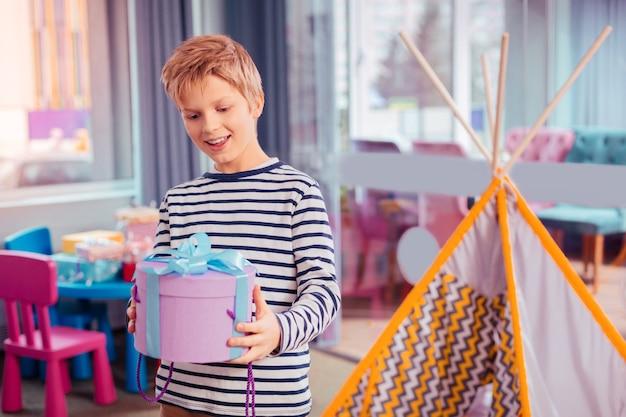 To niespodzianka. wesoły rudowłosy mężczyzna utrzymujący uśmiech na twarzy, trzymając prezent w obu rękach