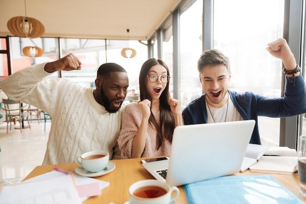 To niewiarygodne. troje młodych ludzi wyrażających emocje siedząc w stołówce i ucząc się.