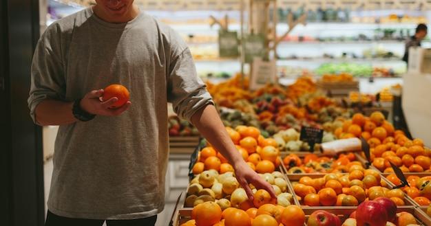 To powinno być w porządku. przystojni młodzi mężczyźni trzymający pomarańczę i torbę na zakupy stojąc w sklepie spożywczym