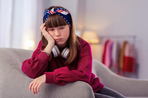 To szkoda. znudzona dziewczyna naciskając usta siedząc na pierwszym planie