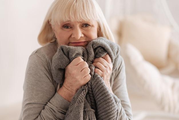 To takie trudne. przygnębiona nieszczęśliwa starsza kobieta trzymająca dzianinową kurtkę zmarłego męża i przyciskająca ją do niej, próbując powstrzymać łzy