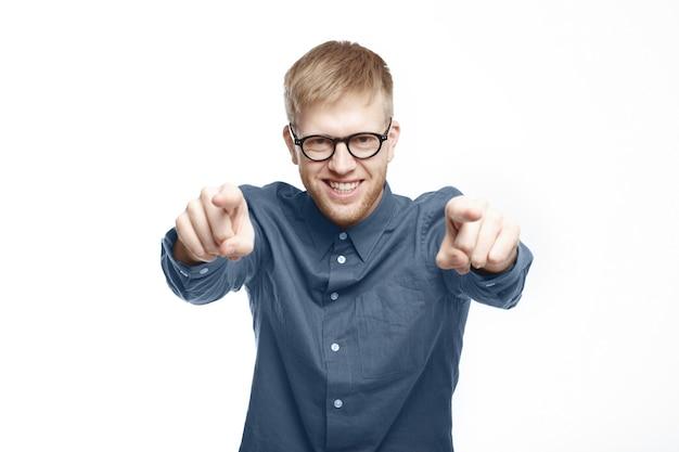 To twoja szansa. przystojny, pewny siebie młody nieogolony mężczyzna w stylowych okularach i brązowej koszuli, wskazując palcami wskazującymi, wybierając ciebie, uśmiechając się podekscytowany, pozowanie