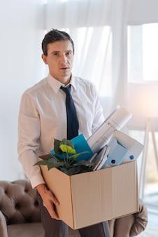 To wszystko. spokojny, zmęczony smutny mężczyzna stojący w lekkim biurze z ciężkim pudełkiem rzeczy osobistych, zdając sobie sprawę, że jego błyskotliwa kariera dobiega końca