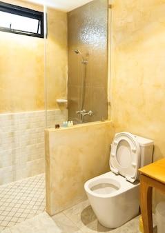 Toaleta w nowoczesnej łazience, wewnętrzna wygodna łazienka, mała współczesna łazienka z prysznicem ze szklanymi drzwiami