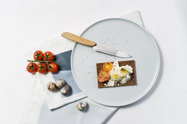 Toast z jajkiem przepiórczym. składniki pomidory, jajko, ser, chleb żytni.