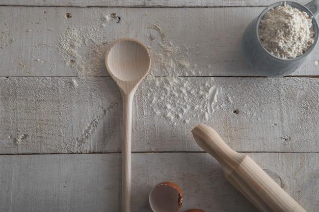 Toczna szpilka i drewniana łyżka dla robić ciastu na białym drewnianym tle.