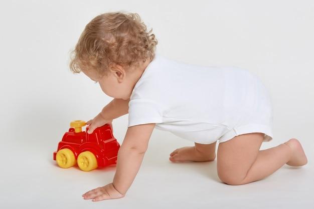 Toddler chłopiec dziecko bawi się autko, pozowanie na czworakach na białym tle nad białym