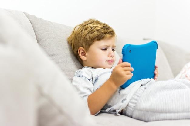 Toddler chłopiec siedzi na kanapie za pomocą tabletu