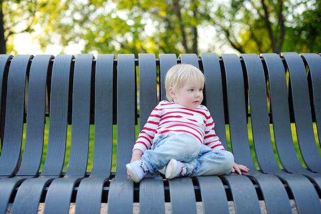Toddler chłopiec siedzi na ławce na zewnątrz