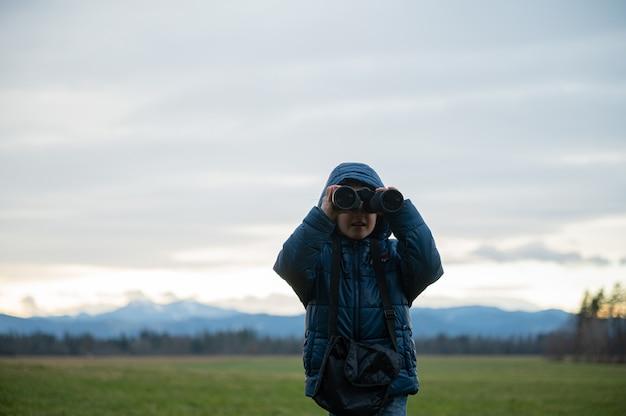 Toddler chłopiec stojący na zewnątrz na pięknej łące obserwując przyrodę z lornetką skierowaną w kamerę.