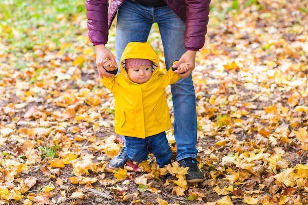 Toddler chłopiec trzymając się za ręce z ojcem hir na zewnątrz w dzień jesieni