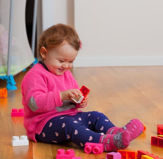Toddler dziewczynka bawi się z gumowych bloków konstrukcyjnych.