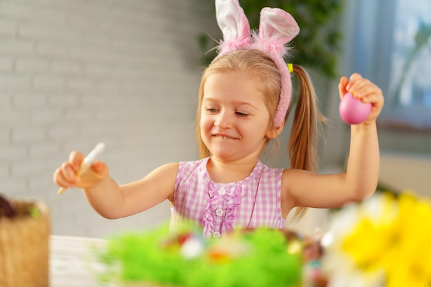 Toddler dziewczynka z bunny uszy farbowanie jaj na wielkanoc