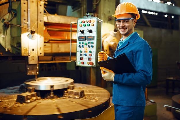 Tokarz w mundurze i hełmie stojący przy zautomatyzowanej tokarce, fabryka. produkcja przemysłowa, metaloplastyka, produkcja maszyn energetycznych