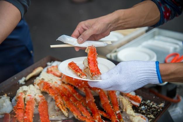 Tokio, japonia ulica na targu zewnętrznym tsukiji w ginza z ekspozycją detaliczną z bliska gotowanych czerwonych kraba udka homara z białym mięsem