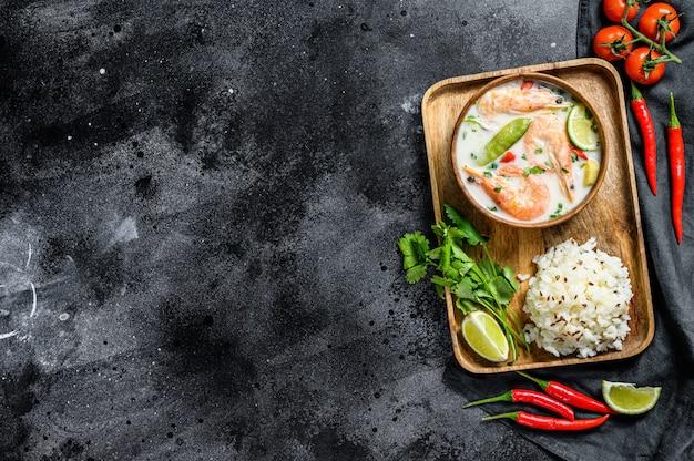 Tom kha gai. pikantna kremowa zupa kokosowa z kurczakiem i krewetkami. tajskie jedzenie. czarna powierzchnia. widok z góry. skopiuj miejsce