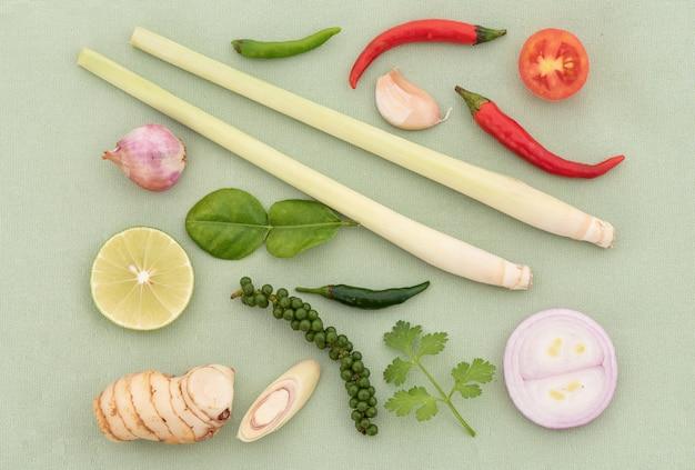 Tom mniam zawiera chili, szalotkę, trawę cytrynową, liście limonki kaffir, cytrynę, galangal, kolendrę, cebulę na zielonym tle. widok z góry, układ płaski.