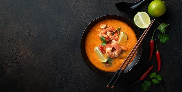 Tom yum kung pikantna tajska zupa z krewetkami w czarnej misce na ciemnym tle widok z góry